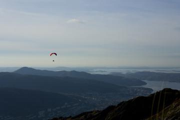 Paraglider flying over Norwegian coastal landscape