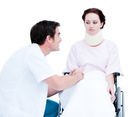 Attentive male doctor discussing with a patient in a wheelchair