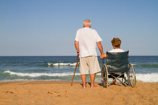 senior man and wheelchair wife on beach
