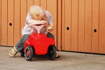 Child sitting on a red car