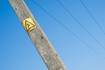 Danger of electrocution sign on electric pole on blue sky