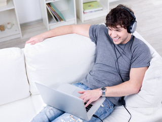 Young man relaxing with laptop and headset