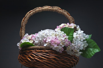 Basket of artificial flowers against dark background