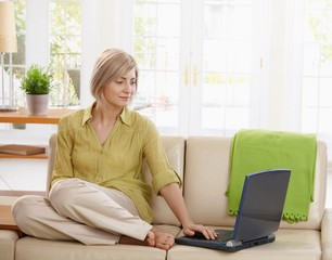 Woman using computer on couch
