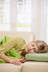 Blond woman sleeping on couch