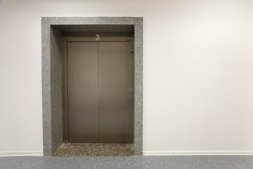 Metal door of elevator on third floor office building.