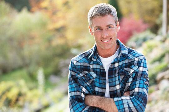 Portrait Of Man Standing Outside In Autumn Landscape