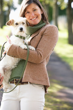 Woman Walking Dog Outdoors In Autumn Park