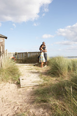 Romantic Young Couple Standing By Wooden Fence Of Beach Hut Amon