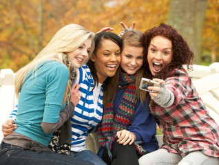 Group Of Four Teenage Girls Taking Picture With Camera Sitting O
