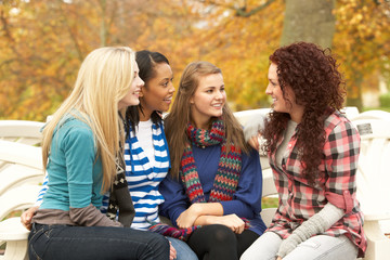 Group Of Four Teenage Girls Sitting And Chatting On Bench In Aut