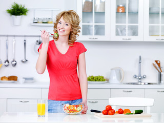 Woman with healthy food in the kitchen