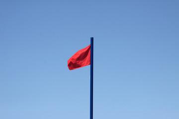 Czerwona ostrzegawcza flaga na plaży na niebieskim niebie