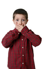 Young boy in plaid shirt with hands over mouth, studio shot
