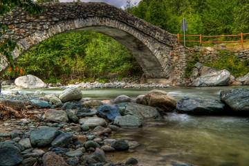Ponte romano su torrente di pietre in alta montagna
