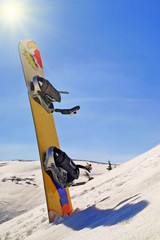 Snowboard in a snow on the mountain slope