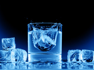 Close up view of the glass and ice cubes on black