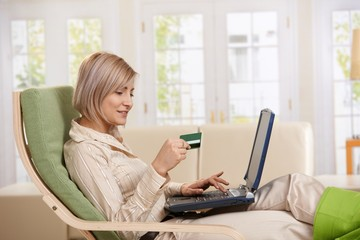 Woman using credit card on Internet.