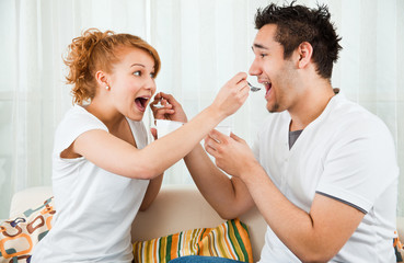 young, beauty girl and a handsome boy eating yoghurt