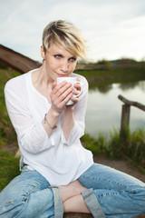 junge frau entspannt mit einer tasse kaffee am seeufer
