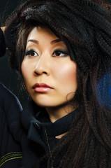 portrait of beauty brunette asian girl on black background