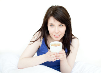 Charming woman drinking a coffee sitting on her bed