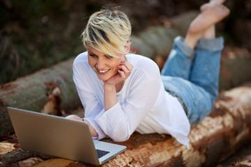 junge frau arbeitet mit laptop in der natur