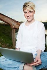 junge frau arbeitet mit dem laptop am seeufer