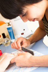 Manicurist polishing client's nails