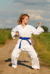 karate training young girl on the meadow