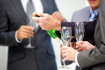 Close-up of a business man opening a bottle of Champagne