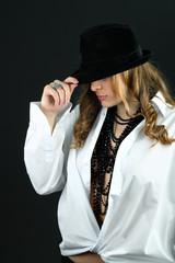 Girl in white shirt hiding her face under black hat