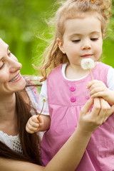 Mom giving dandelion to daughter