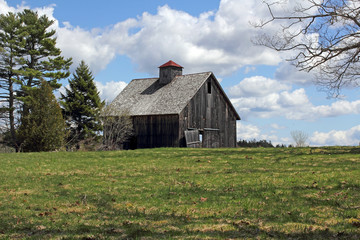 Old worn barn in field with bright cloudy sky