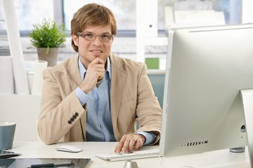 Young businessman thinking at desk