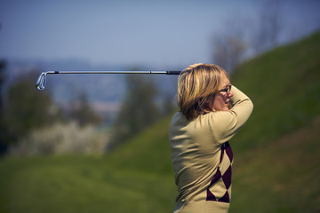 Portrait of woman golfer after a swing from profile