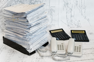 Heap of design and project drawings, calculators and telephones
