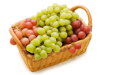 Wattled basket with grapes isolated on white