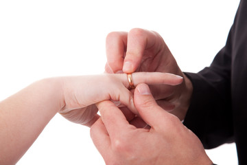 hand of a man putting a ring on the hand of a woman