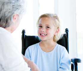 Blond little girl sitting on a wheelchair talking with her grand