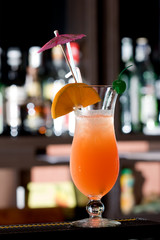 Fresh iced cocktail garnished orange and umbrella.