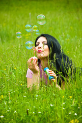 Lying in field and blowing soap bubbles