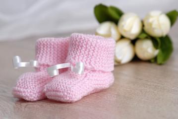 chaussons de bébé rose sur surface de bois