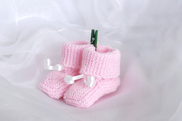 chaussons de bébé rose sur fond de mousseline blanc