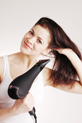 Beautiful smiling woman drying her hair with a blow dryer
