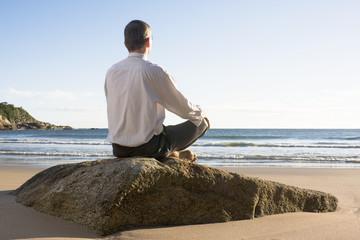 Geschäftsmann sitzt auf Fels am Meer