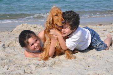 2 enfants et leur chien heureux sur la plage