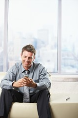 Businessman looking at mobile on sofa.