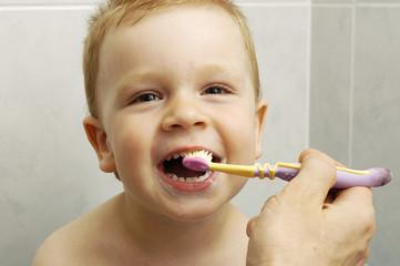 Toddler boy brushes his teeth