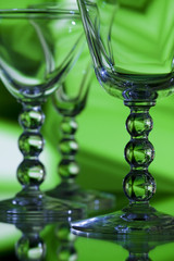Beautiful wine glasses on abstract green background